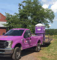 Toilet rental service truck in New York and purple porta potty
