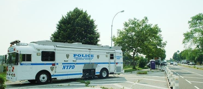 John to Go portable bathroom rental in NY near an NYPD truck